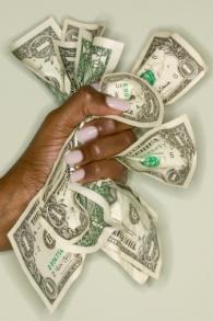 Woman's hand crushing bank notes